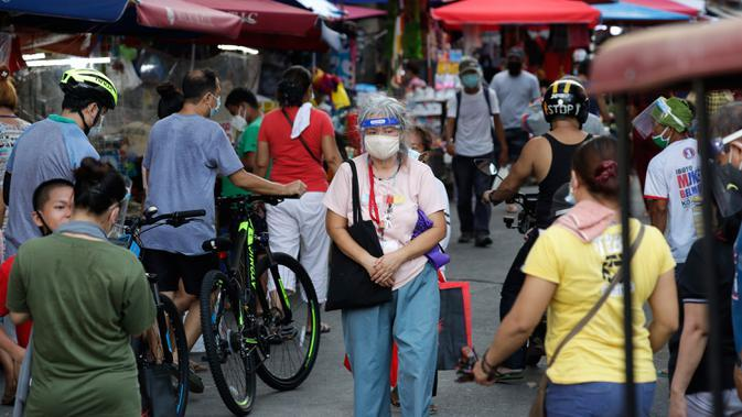 Seorang perempuan yang mengenakan masker berjalan di sepanjang kios darurat, setelah pelonggaran lockdown, di pusat kota Manila, Filipina, Rabu (2/9/2020). Pemerintah melonggarkan lockdown meskipun negara tersebut memiliki infeksi virus corona terbanyak di Asia Tenggara. (AP Photo/Aaron Favila)