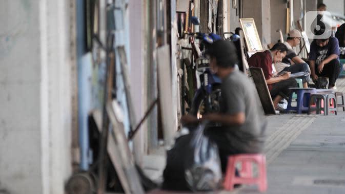 Seniman lukis menyelesaikan karyanya di pinggir Jalan Pintu Besar Selatan, Pinangsia, Jakarta, Selasa (2/6/2020). Sejumlah seniman memilih tutup sementara di tengah pandemi virus corona COVID-19, sedangkan beberapa lainnya tetap bertahan demi mendapatkan penghasilan. (merdeka.com/Iqbal S. Nugroho)