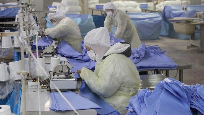 Pekerja memproduksi pakaian pelindung di sebuah pabrik di Nantong, Provinsi Jiangsu, China, Senin (27/1/2020). Pakaian pelindung tersebut diproduksi untuk mendukung pasokan bahan medis saat wabah virus corona melanda China. (STR/AFP)
