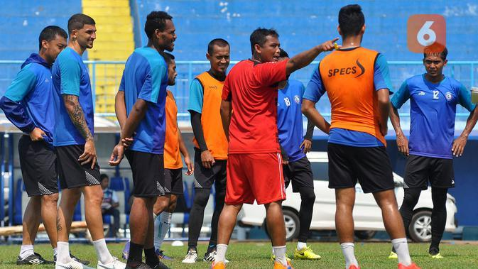 Asisten pelatih Arema, Kuncoro, memberikan instruksi kepada deratan pemain belakang. (Bola.com/Iwan Setiawan)