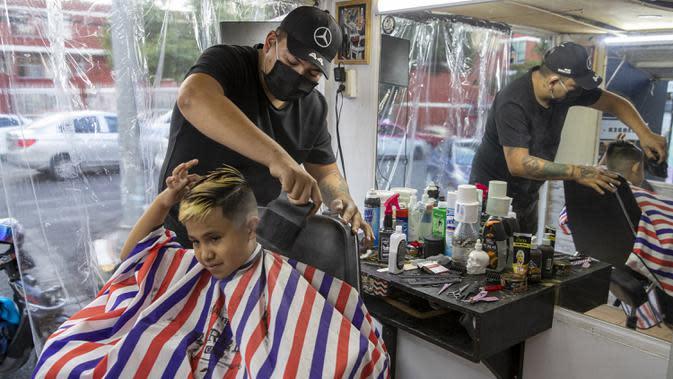 Gerardo (belakang) memangkas rambut pelanggan dalam salon rambut keliling miliknya di Mexico City, Meksiko, 6 Agustus 2020. Gerardo mengubah sebuah mobil van menjadi salon rambut keliling yang menawarkan jasa pangkas rambut kepada warga Mexico City di tengah pandemi COVID-19. (Xinhua/Ricardo Flores)