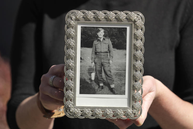 In this Wednesday, April 8, 2020, photo, Kelly Adsero holds a family photo of her grandfather Bill Chambers that shows him when he was a young solider in the Canadian Army. Chambers, 97, died March 14, 2020, at an adult family home where he lived with four other World War II veterans. He wasn't obviously ill, but tested positive for the new coronavirus after he died. (AP Photo/Ted S. Warren)