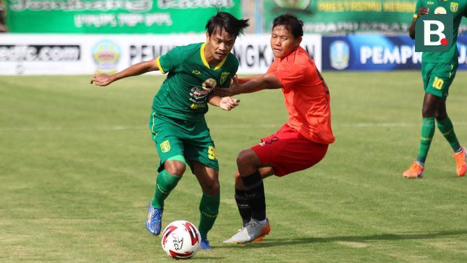 Duel antara pemain Persebaya Surabaya, M. Hidayat, dan gelandang Bhayangkara FC, Adam Alis, saat pertandingan Grup A Piala Gubernur Jatim 2020 di Stadion Bangkalan, Rabu (12/2/2020). (Bola.com/Aditya Wany)