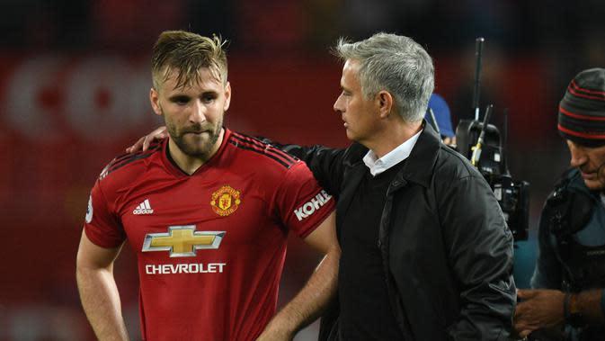 Pelatih Manchester United, Jose Mourinho merangkul bek Luke Shaw usai pertandingan melawan Tottenham Hotspur pada lanjutan Liga Inggris di Old Trafford, (27/8). MU kalah telak atas tottenham 3-0. (AFP Photo/Oli Scarff)
