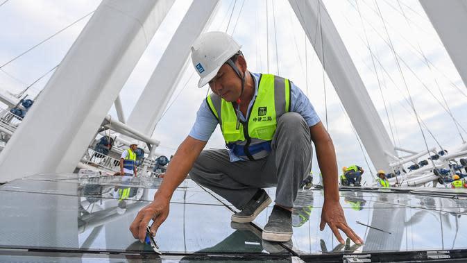 Seorang staf bekerja di lokasi pembangunan sebuah kincir ria di taman budaya pesisir Baoan di Shenzhen, Provinsi Guangdong, China selatan (6/10/2020). Kincir ria setinggi 128 meter tersebut saat ini sedang dalam tahap pembangunan. (Xinhua/Liu Dawei)