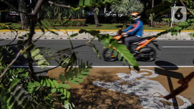 Kendaraan Roda dua melintasi Jalur Khusus Sepeda Motor dijalan Medan Merdeka Barat, Jakarta, Jumat (21/8/2020). Dalampergubtersebut Pemprov DKI Jakarta mengatur kendaraan yang diperkenankan melintas di wilayahganjil genap.(Liputan6.com/Johan Tallo)
