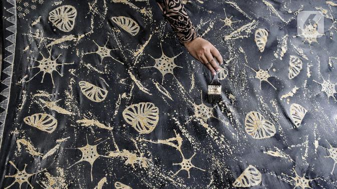 Perajin menyelesaikan pembuatan batik bermotif Covid-19 di Rumah Batik Palbatu, Jakarta, Kamis (15/10/2020). Sempat tutup akibat pandemi, Rumah Batik Palbatu perlahan bangkit dengan menciptakan kain batik edisi Jakarta Terkini bergambar Covid-19 dipadu ikon-ikon Ibu Kota. (merdeka.com/Iqbal Nugroho)