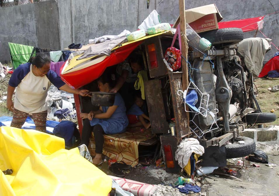 Homeless residents sit inside makeshift shelter after super typhoon Haiyan hit Tacloban