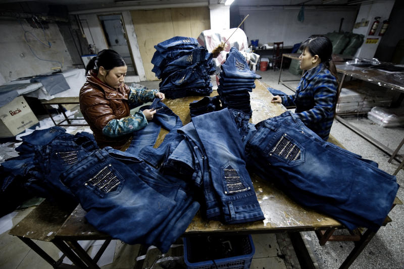 """XINTANG, CHINA - FEBRUARY 10: Workers sew blue jeans in a little workshop by the street on February 10, 2012 in Xintang, Guangdong province, China.The town of Xintang, nicknamed """"the denim jeans center of the world, claims to produce 60% of the world global output of jeans. (Photo by Lucas Schifres/Getty images)"""