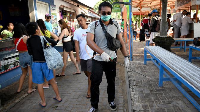 Seorang petugas kesehatan (kanan) menyemprotkan disinfektan di kawasan wisata di Sanur, Bali, Senin (16/3/2020). Penyemprotan dilakukan sebagai salah satu langkah untuk mengantisipasi potensi penyebaran virus Corona COVID-19 di kawasan pariwisata tersebut. (SONNY TUMBELAKA/AFP)