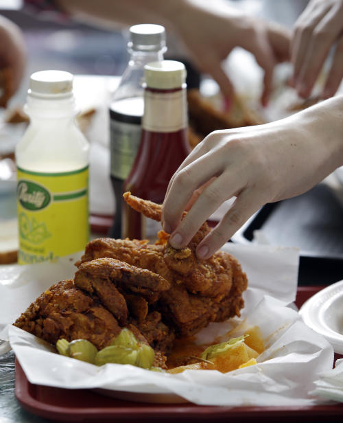 In this Friday, March 23, 2013 photo, a diner reaches for a piece of hot chicken at Prince's Hot Chicken Shack in Nashville, Tenn. Hot chicken -- fried chicken with varied amounts of seasoning that make the heat level run from mild to extra hot -- is a signature dish of Nashville. (AP Photo/Mark Humphrey)