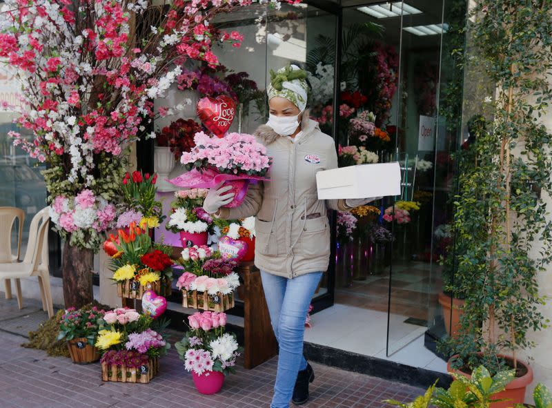A woman holds flowers as she leaves a flower shop that is open exceptionally for Mother's Day, in Beirut