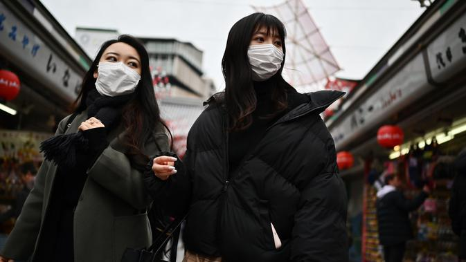 Dua wanita memakai masker berjalan di sepanjang jalan dekat kuil Sensoji di daerah Taito Tokyo (27/1/2020). Masker dipilih sebagai salah satu tindak pencegahan sederhana dari virus dengan karakteristik mirip SARS tersebut. (AFP Photo/Charly Triballeau)