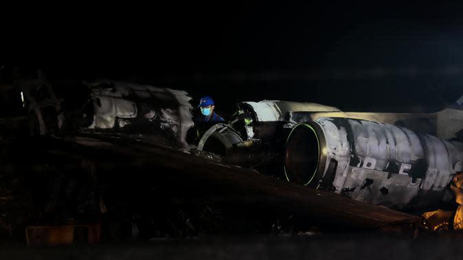 Petugas memeriksa puing-puing pesawat yang mengalami kecelakaan di ujung landasan pacu 24 di Bandara Internasional Ninoy Aquino, Manila, Filipina (29/3/2020). Pesawat Lionair ini berbeda dengan pesawat maskapai Lion Air di Indonesia. (Xinhua/Rouelle Umali)