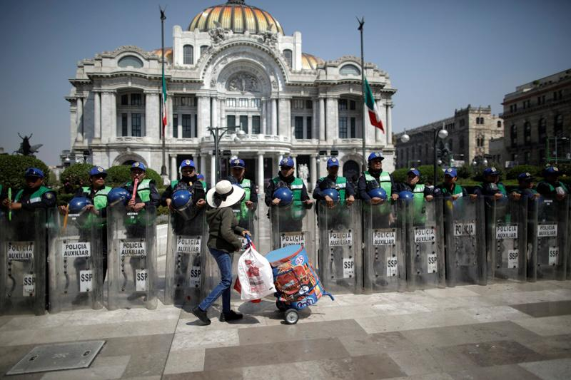 Security forces patrol as demonstrators take part in a protest against gender-based violence outside the Palacio de Bellas Artes in Mexico City