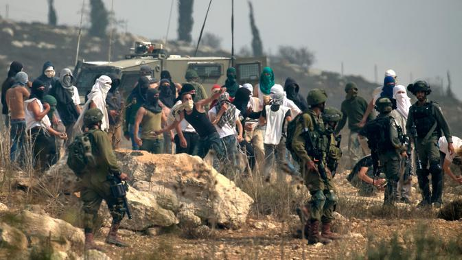 Tentara Israel berdiri ketika pemukim Israel bertopeng melemparkan batu ke arah demonstran Palestina (tak terlihat) yang berkumpul selama demonstrasi menentang pembangunan pos terdepan Israel di dekat desa Palestina, Ramallah, Tepi Barat, Kamis (17/10/2019). (JAAFAR ASHTIYEH/AFP)