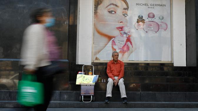 Tomas Gonzalez, 80, menjual masker dan gel antibakteri untuk pejalan kaki di Mexico City (23/3/2020). Gonzalez dan istrinya yang pernah menjual sandwich, kini beralih menjual produk-produk yang terkait dengan virusona minggu lalu. (AP Photo/Rebecca Blackwell)