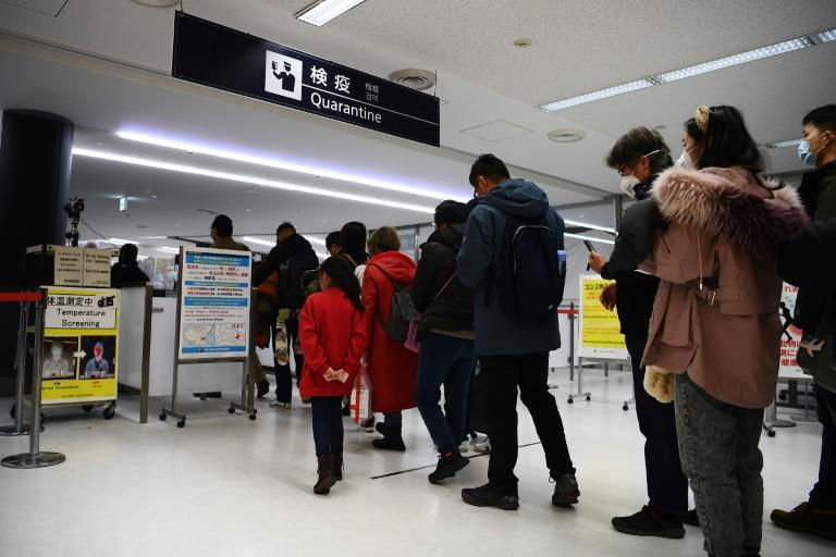 Passengers who arrived on one of the last flights from the Chinese city of Wuhan walk through a health screening station at Narita airport in Chiba prefecture, outside Tokyo
