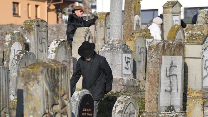 Orang-orang melihat makam yang dicoreti lambang swastika Nazi di pemakaman Yahudi, Westhoffen, dekat Strasbourg, Prancis, Rabu (4/12). Sedikitnya 107 makam menjadi sasaran vandalisme dengan dicoreti lambang swastika Nazi. (AFP/Patrick Hertzog)