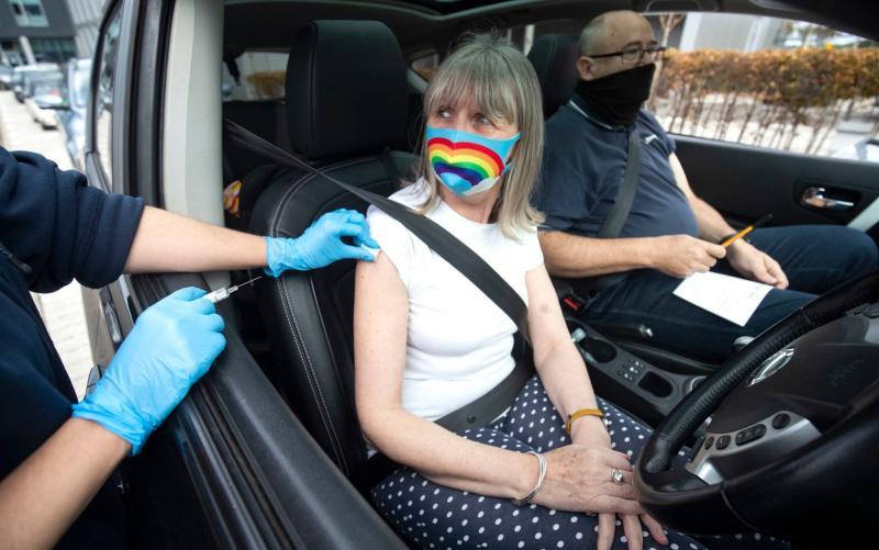 A member of the public receives a flu vaccine while sitting in her car at a drive-through flu clinic in Edinburgh - Jane Barlow/PA
