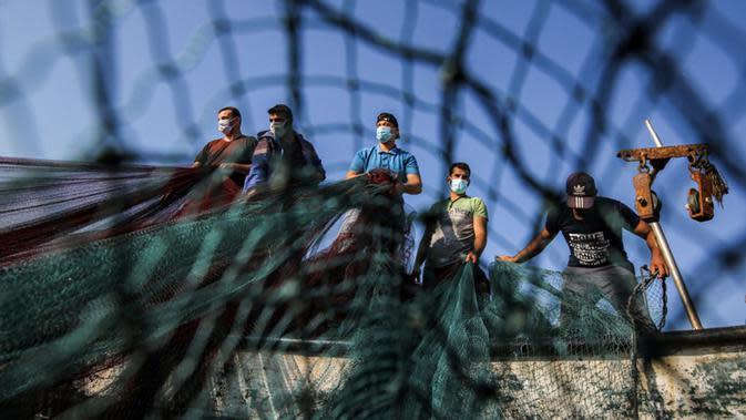 Nelayan Palestina yang mengenakan masker karena pandemi virus corona COVID-19 menyiapkan jala ikan di sepanjang pantai Laut Mediterania, Rafah, Jalur Gaza, Rabu (2/9/2020). (SAID KHATIB/AFP)