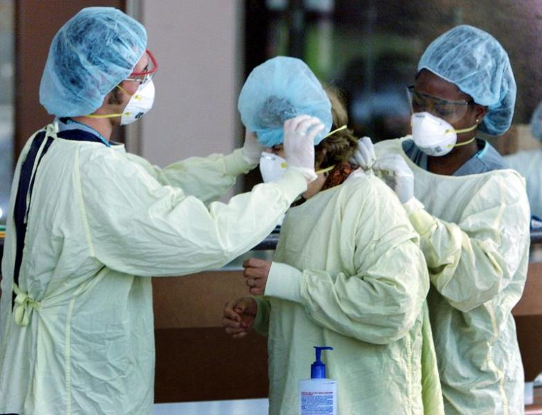 FILE PHOTO: HOSPITAL WORKERS HELP A VISITOR PUT ON CLOTHING TO PROTECT AGAINSTSARS.
