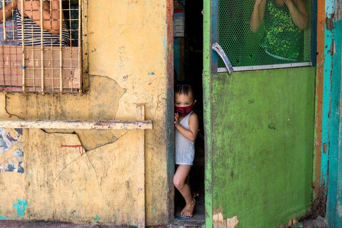 A small child in a face mask looks out a doorway