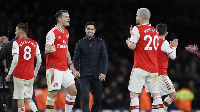 Manajer Arsenal Mikel Arteta (tengah) bersama fans merayakan kemenangan atas Everton pada pekan ke-27 Liga Inggris. Arsenal menang 3-2 di Emirates Stadium, Senin (24/2/2020) dini hari WIB. (Foto AP / Kirsty Wigglesworth)