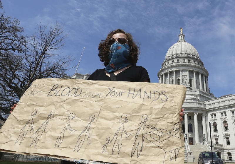 Maya Banks, of Madison, Wis., expresses her opposition to decisions by the state's legislature and Supreme Court to proceed with a the state's primary election while holding a sign outside the Wisconsin State Capitol building in Madison, Tuesday, April 7, 2020. (John Hart/Wisconsin State Journal via AP)