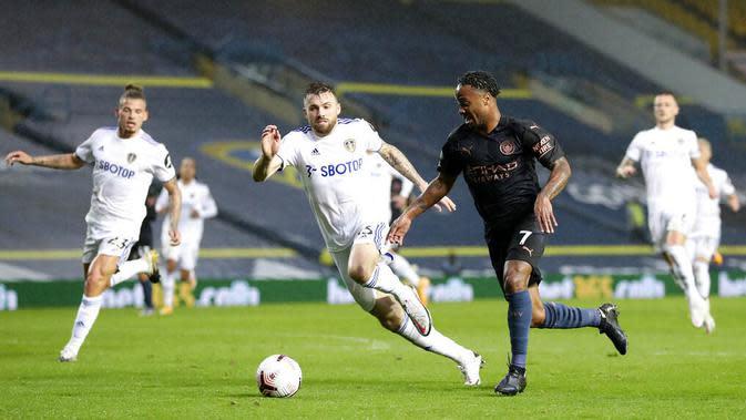 Penyerang Manchester City, Raheem Sterling, berusaha melewati pemain Leeds United pada laga Liga Inggris di Stadion Elland Road, Sabtu (3/10/2020). Kedua tim bermain imbang 1-1. (Cath Ivill/Pool via AP)