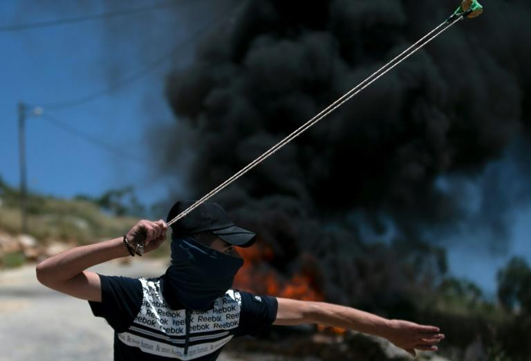 A Palestinian youth uses a slingshot to hurl rocks at Israeli troops during clashes in the West Bank village of Kfar Qaddum on May 8