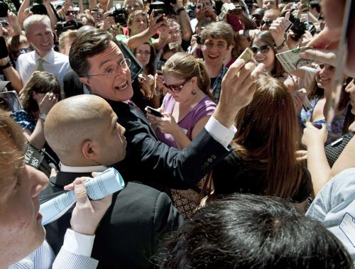 Comedian Stephen Colbert collects cash donations on the sidewalk in front of the Federal Election Commission in Washington, Thursday, June 30, 2011, after a hearing on his request to form a Political Action Committee. (AP Photo/Cliff Owen)