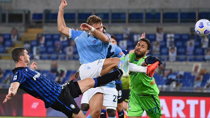 Striker bintang Lazio, Ciro Immobile (tengah) berebut bola dengan kiper Atalanta Marco Sportiello pada laga kedua Liga Italia Serie A di Stadion Olimpiade, Rabu (30/9/2020). Atalanta mampu menaklukkan tuan rumah Lazio dengan skor 4-1. (Alfredo Falcone/LaPresse via AP)