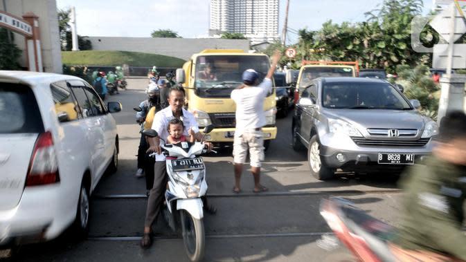 Warga mengatur lalu di perlintasan kereta api di Jalan Duri Kosambi Raya, Jakarta, Rabu (15/1/2020). Warga setempat membangun palang secara swadaya dan mengatur lalu lintas akibat perlintasan kereta dekat Stasiun Rawa Buaya tersebut belum dipasang palang pintu otomatis. (merdeka.com/Iqbal Nugroho)