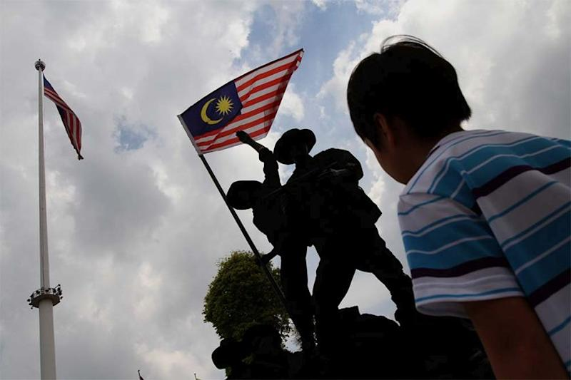 A boy looks at a replica of Tugu Negara at Dataran Merdeka. Malaysia will celebrate its 57th year of independence on August 31, 2014. — Picture by Yusof Mat Isa