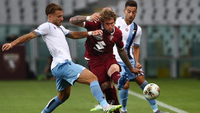 Bek Torino, Lyanco (tengah) berusaha melewati dua pemain Lazio pada pertandingan lanjutan Liga Serie A Italia di stadion Olimpiade di Turin (30/6/2020). Lazio menang tipis atas Torino 2-1. (AFP Photo/Isabella Bonotto)