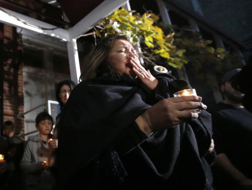 Chef Priscila Satkoff fights back tears during a candlelight memorial for Chicago Chef Charlie Trotter outside Trotter's former restaurant Tuesday, Nov. 5, 2013, in Chicago. Trotter, 54, died Tuesday, a year after closing his namesake Chicago restaurant that was credited with putting his city at the vanguard of the food world and training dozens of the nation's top chefs, including Grant Achatz and Graham Elliot. (AP Photo/Charles Rex Arbogast)