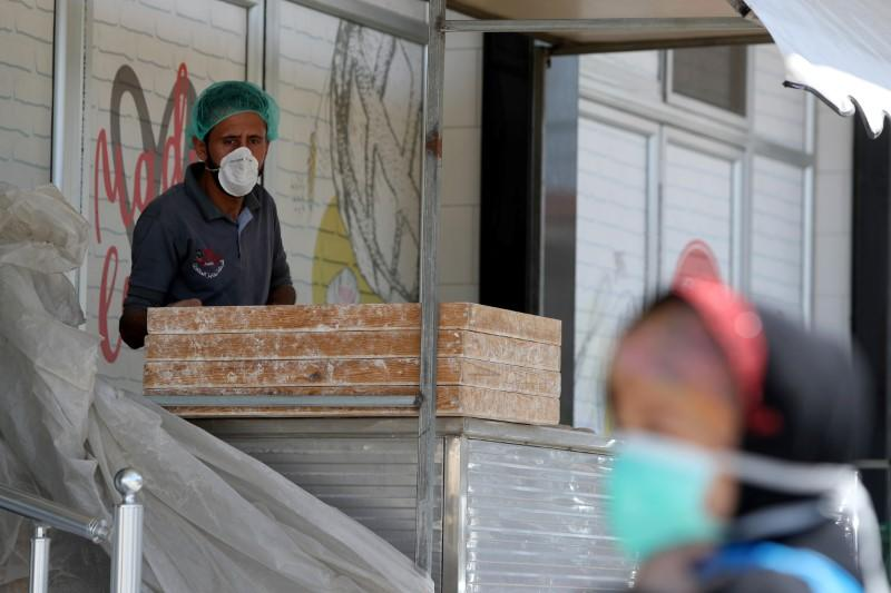 Palestinian man, wearing a mask as a preventive measure against the coronavirus disease, looks on as he works at a bakery in Gaza City