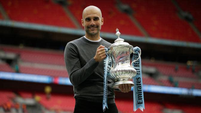 Manajer Manchester City Pep Guardiola berpose dengan trofi Piala FA 2018/2019 di Stadion Wembley, London, Inggris, Sabtu (18/5/2019). The Citizens menjuarai Piala FA 2018/2019 usai mengalahkan Watford dengan skor 6-0. (AP Photo/Tim Ireland)