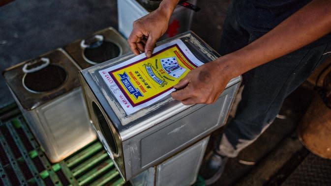 Pekerja menempelkan stiker pada kaleng di Pabrik Kopi Antong, Taiping, Perak, Malaysia, 29 September 2020. Pabrik Kopi Antong menggunakan mesin antik dan metode pemanggangan tradisional untuk menghasilkan bubuk sarat kafein yang terkenal selama 87 tahun. (Mohd RASFAN/AFP)