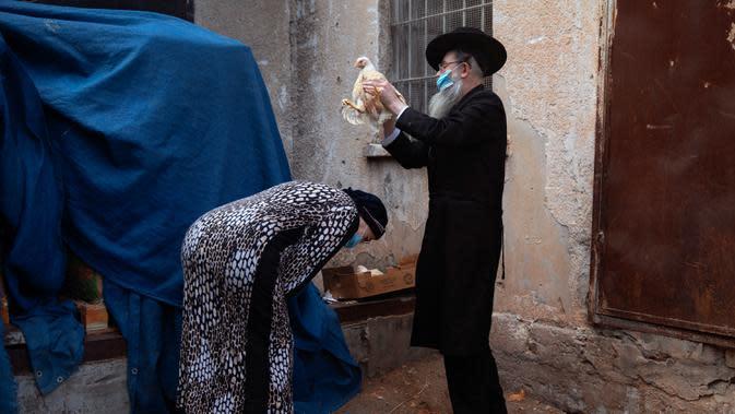 Seorang pria Yahudi ultra-Ortodoksmengayunkan seekor ayam di atas kepala istrinya sebagai bagian dari ritual Kaparot di Bnei Brak, Israel, Rabu (23/9/2020). Tradisi itu digelar sebelum perayaan Yom Kippur atau hari Penebusan dosa, hari paling suci dalam tahun Yahudi. (AP Photo/Oded Balilty)