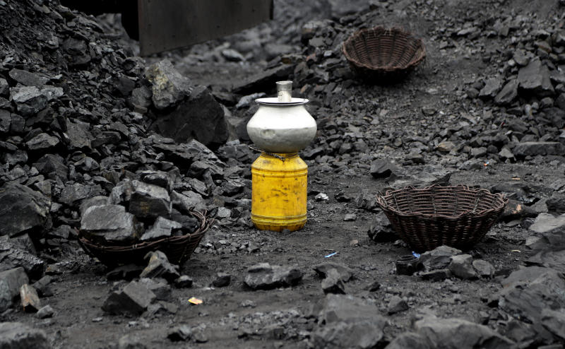 In this Oct. 23, 2019, photo, a metal vessel filled with drinking water stands at a coal loading site in the village of Godhar in Jharia, a remote corner of eastern Jharkhand state, India. The fires started in coal pits in eastern India in 1916. More than a century later, they are still spewing flames and clouds of poisonous fumes into the air, forcing residents to brave sizzling temperatures, deadly sinkholes and toxic gases. (AP Photo/Aijaz Rahi)