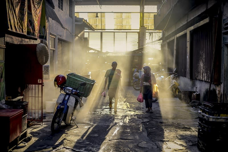 Rays of light stream through open windows at a wholesale wet market in Chow Kit as people go about their morning routine in Kuala Lumpur February 28, 2018. — Picture by Firdaus Latif