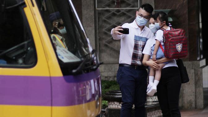 Seorang anak berfoto dengan orang tuanya sebelum menaiki bus sekolah di Hung Hom, Hong Kong, China selatan, pada 29 September 2020. Aturan menjaga jarak sosial (social distancing) sebagian telah dilonggarkan dan kehidupan masyarakat mulai kembali normal. (Xinhua/Wang Shen)