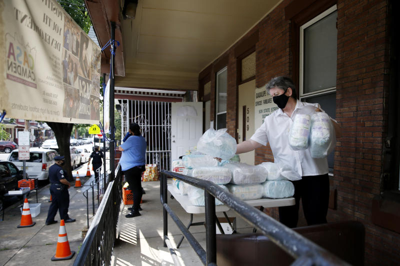 In this June 11, 2020, photo Sister Helen Cole, with Guadalupe Family Services, stacks diapers to distribute to families in Camden, N.J. (AP Photo/Matt Slocum)