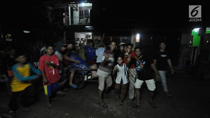 Sejumlah anak menabuh alat musik dari tong sampah berkeliling kampung di kawasan Mekarsari, Depok, Jawa Barat, Rabu (8/5/2019). Kegiatan tersebut merupakan tradisi selama bulan ramadan membangunkan warga untuk sahur. (Liputan6.com/Herman Zakharia)