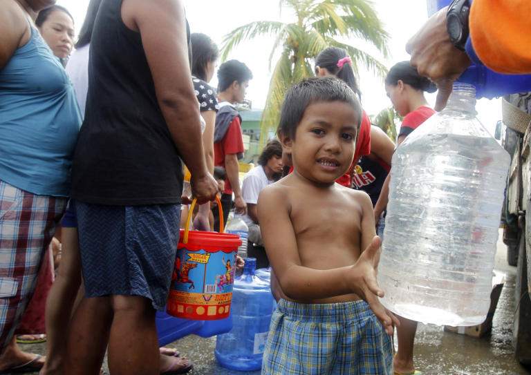 A boy fills up a plastic bottle with water after super typhoon Haiyan hit Tacloban