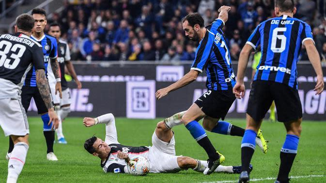 Striker Juventus, Cristiano Ronaldo, berebut bola dengan bek Inter Milan, Diego Godin, pada laga Serie A di Stadion San Siro, Milan, Minggu (6/10). Inter kalah 1-2 dari Juventus. (AFP/Alberto Pizzoli)