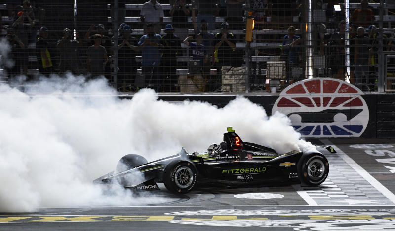 FILE - In this June 8, 2019, file photo, Josef Newgarden does a burnout after winning the IndyCar auto race at Texas Motor Speedway in Fort Worth, Texas. IndyCar opens its pandemic-delayed season with an all-in-one-day show Saturday on the fast high-banked 1 ½-mile oval at Texas Motor Speedway, more than eight months after the 2019 finale. (AP Photo/Larry Papke, File)