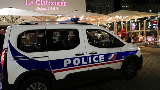 Polisi berpatroli di Lille, Prancis, Jumat (16/10/2020). Prancis mengerahkan 12.000 polisi untuk memberlakukan jam malam baru mulai Jumat malam hingga bulan depan untuk memperlambat penyebaran COVID-19. (AP Photo/Michel Spingler)